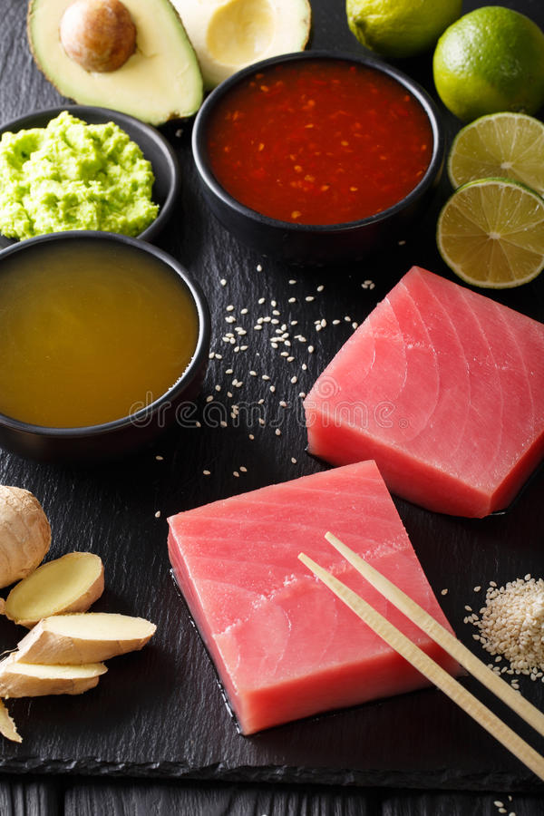Asian style: Raw fresh tuna with ingredients for cooking close-up. vertical. Asian style: Raw fresh tuna with ingredients for cooking close-up on the table stock photography