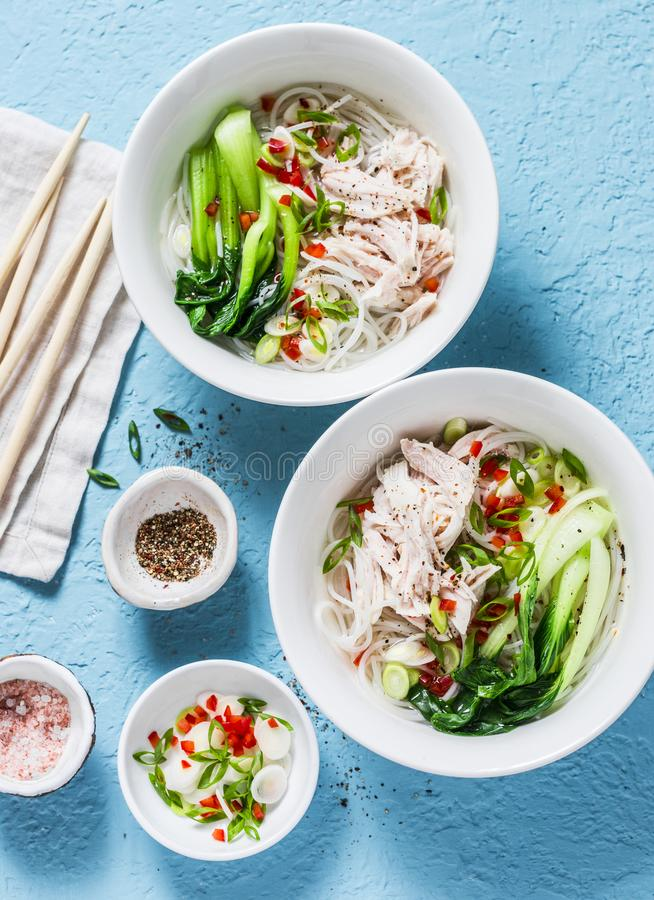 Asian style soup. Rice noodles, boiled chicken, vegetables and broth - delicious diet lunch on blue background, top view. stock photo