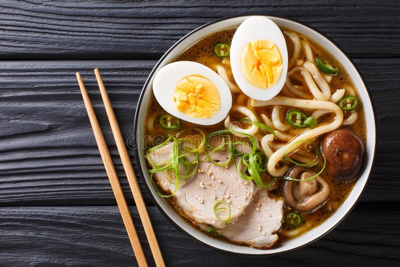 Asian style soup with udon noodles, pork, boiled eggs, mushrooms stock images