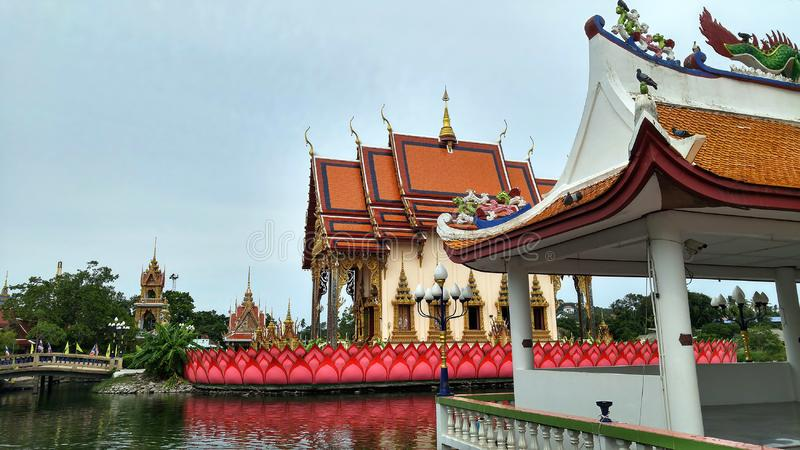 Asian style buddhist temple standing on the lake. Multi colored buildings and a bridge leading inside. Asian style temple standing on the lake. Multi colored stock photos