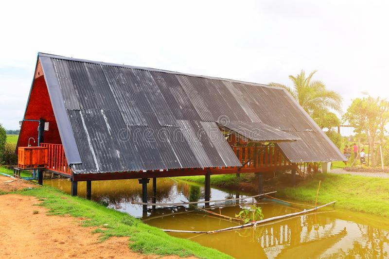 Asian-style Thai house design with low roofs and a river on the bottom. Sun stock photos