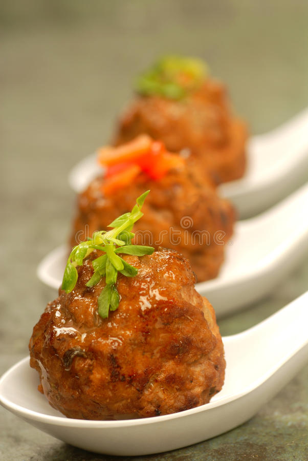 Asian styled meatballs on spoons with a variety of toppings. Delicious homemade Asian styled meatballs on spoons with a variety of toppings royalty free stock photo