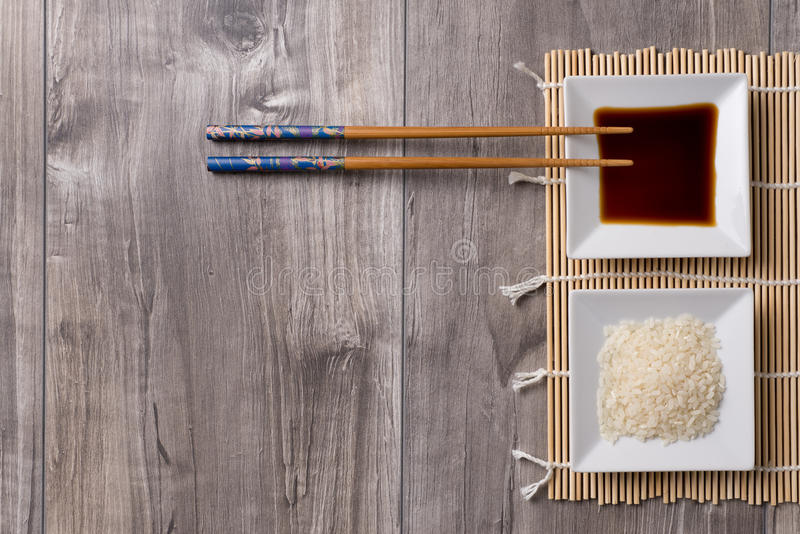 Asian table with chopsticks, soy sauce and rice royalty free stock photography
