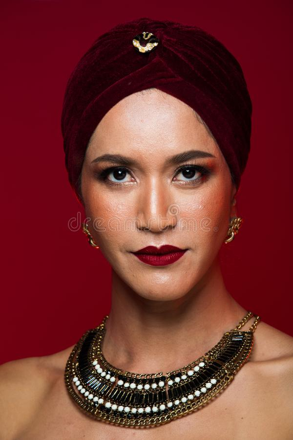 Asian tanned skin woman with strong color red lips. Fashion portrait of Arabian Middle East Muslim woman with strong color red lips, studio lighting red reddish royalty free stock photography