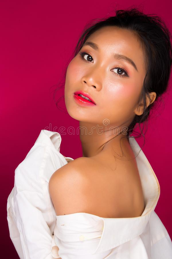 Asian tanned skin woman with strong color red lips. Fashion portrait of Asian Black hair tanned skin woman with strong color red lips, studio lighting red stock image