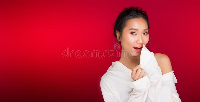 Asian tanned skin woman with strong color red lips. Fashion portrait of Asian Black hair tanned skin woman with strong color red lips, studio lighting red royalty free stock images