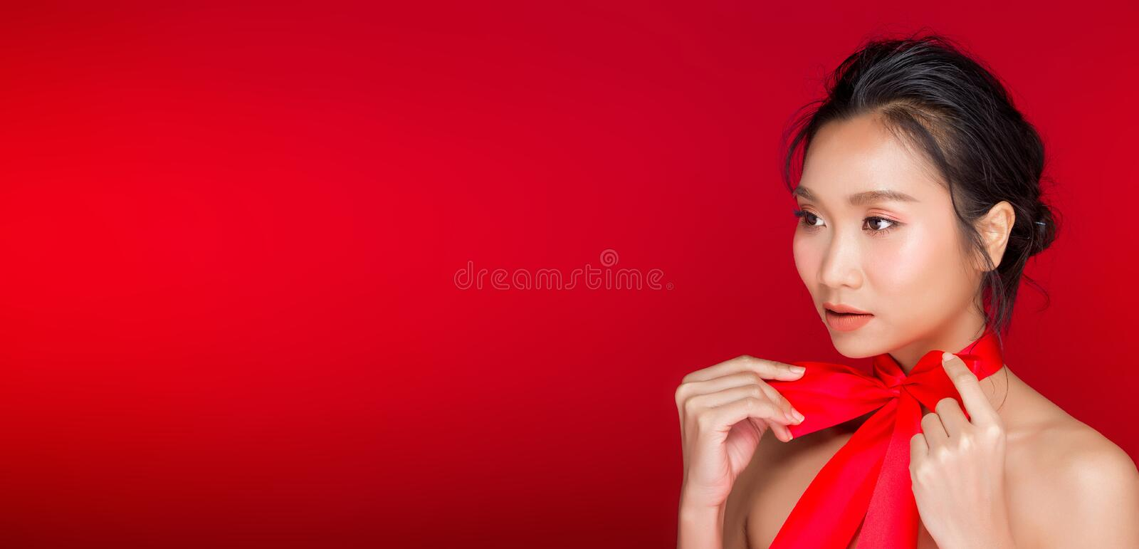 Asian tanned skin woman with strong color red lips. Fashion portrait of Asian Black hair tanned skin woman with strong color red lips, studio lighting red stock images