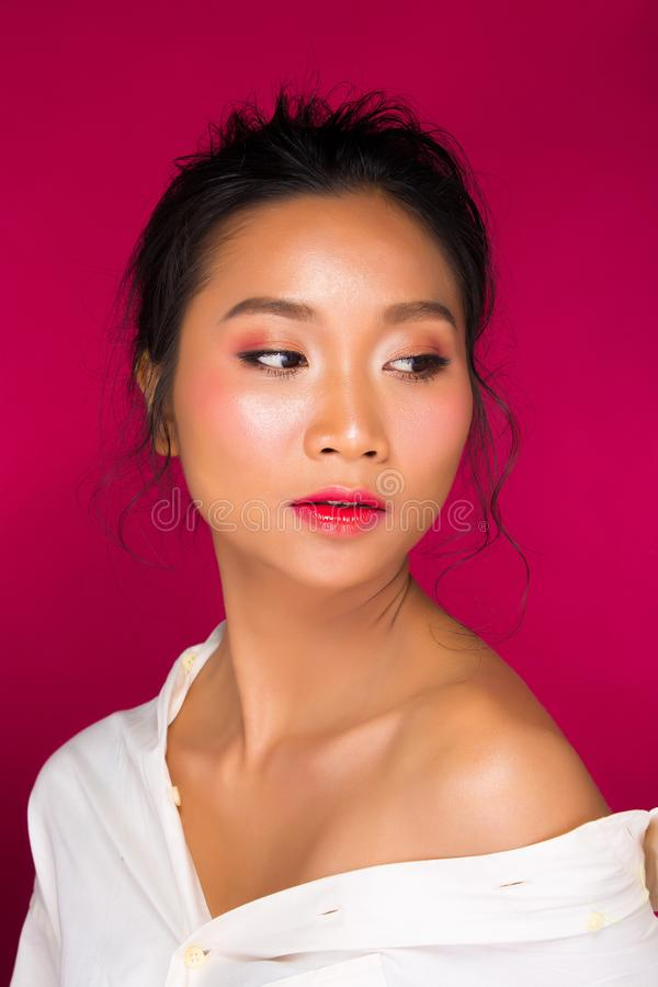 Asian tanned skin woman with strong color red lips. Fashion portrait of Asian Black hair tanned skin woman with strong color red lips, studio lighting red royalty free stock photography