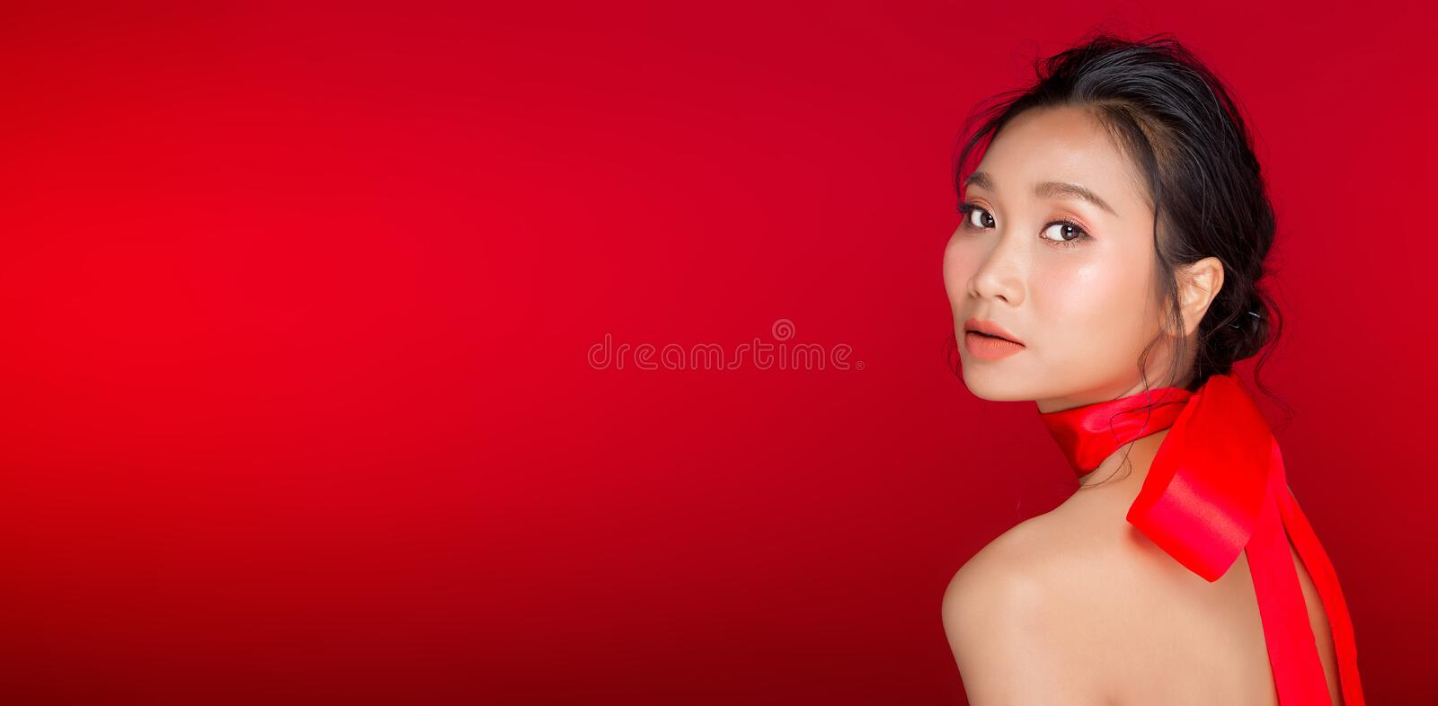 Asian tanned skin woman with strong color red lips. Fashion portrait of Asian Black hair tanned skin woman with strong color red lips, studio lighting red royalty free stock image