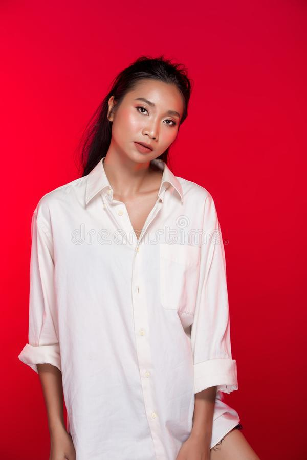 Asian tanned skin woman with strong color red lips. Fashion portrait of Asian Black hair tanned skin woman with strong color red lips, studio lighting red stock photos