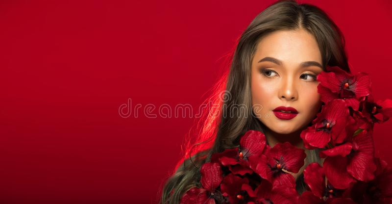 Asian tanned skin woman with strong color red lips. Fashion portrait of Asian Gray curl hair woman with strong color red lips, studio lighting red reddish royalty free stock photo