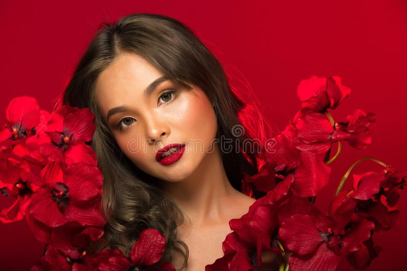 Asian tanned skin woman with strong color red lips. Fashion portrait of Asian Gray curl hair woman with strong color red lips, studio lighting red reddish royalty free stock image