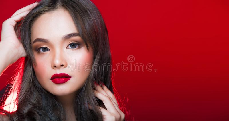 Asian tanned skin woman with strong color red lips. Fashion portrait of Asian Gray curl hair woman with strong color red lips, studio lighting red reddish stock image
