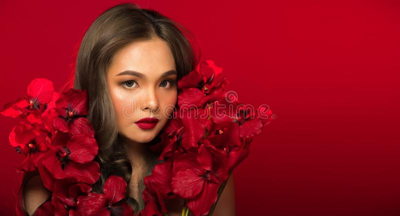 Asian tanned skin woman with strong color red lips. Fashion portrait of Asian Gray curl hair woman with strong color red lips, studio lighting red reddish stock photography
