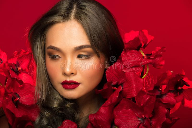 Asian tanned skin woman with strong color red lips. Fashion portrait of Asian Gray curl hair woman with strong color red lips, studio lighting red reddish royalty free stock images