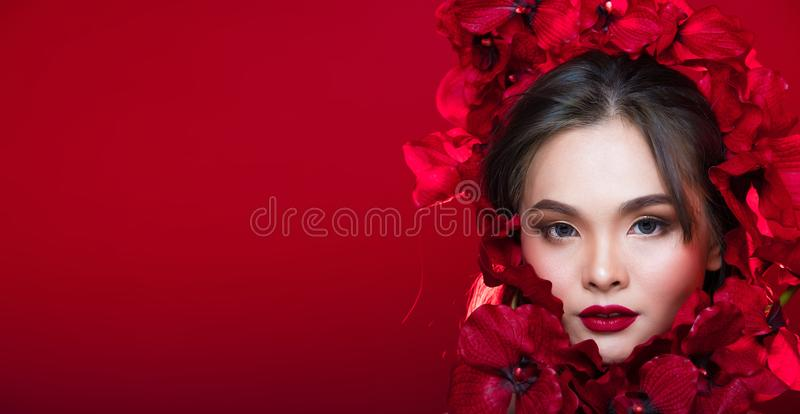 Asian tanned skin woman with strong color red lips. Fashion portrait of Asian Gray curl hair woman with strong color red lips, studio lighting red reddish royalty free stock photography