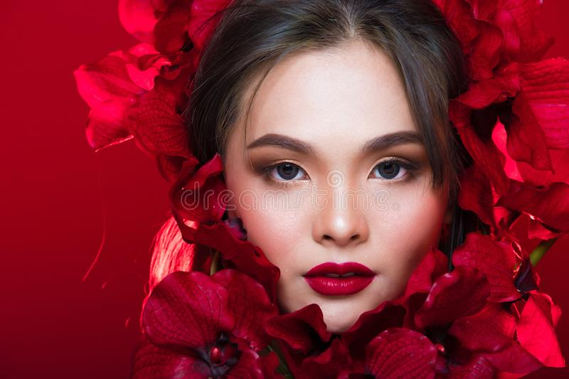 Asian tanned skin woman with strong color red lips. Fashion portrait of Asian Gray curl hair woman with strong color red lips, studio lighting red reddish stock photos
