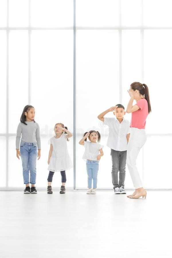 Asian teacher play girls and boy some acting. Asian kids salute to Asian women in pink shirt, she salute backto them, they stand in front of big white window royalty free stock images