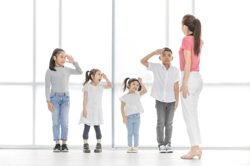 Asian teacher play girls and boy some acting. Asian kids salute to Asian women in pink shirt, she salute backto them, they stand in front of big white window stock images