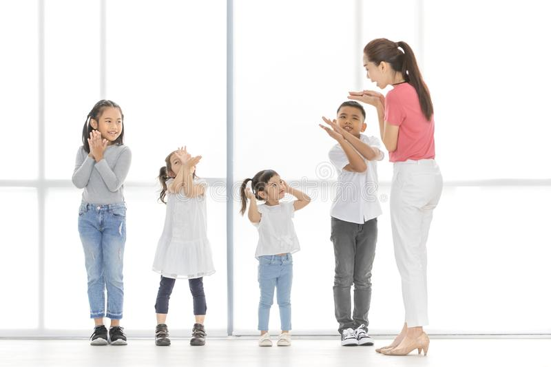 Asian teacher play girls and boy some acting. Asian kids salute to Asian women in pink shirt, she salute backto them, they stand in front of big white window royalty free stock photography