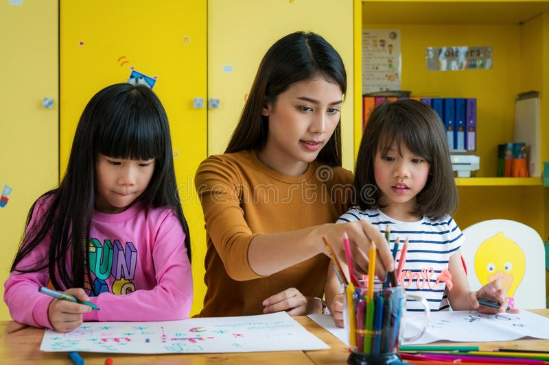 Asian teacher and preschool student in art class stock photo