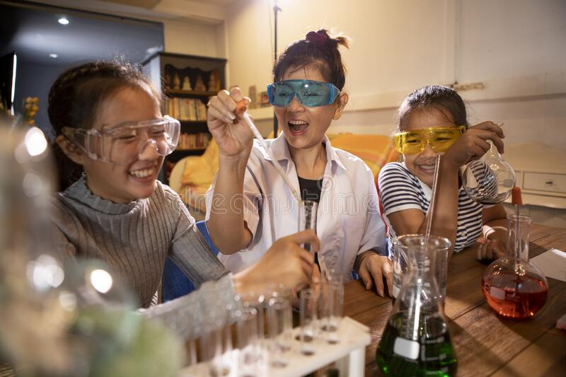 Asian teacher and student in school science laboratory room stock image