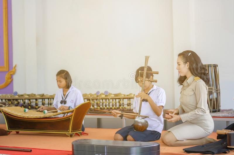 Asian Teacher teaching students to practice Thai instrument royalty free stock images