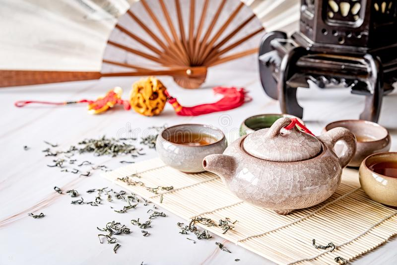 Asian teapot with teacups on bamboo tablamat decorated with chinese fan, lantern and scattered green tea on white marble. Tea ceremony. Asian tea. Asian teapot stock image