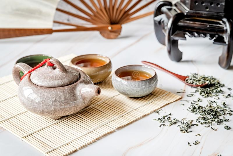 Asian teapot with teacups on bamboo tablamat decorated with chinese fan, lantern and scattered green tea on white marble. Tea ceremony. Asian tea. Asian teapot stock images