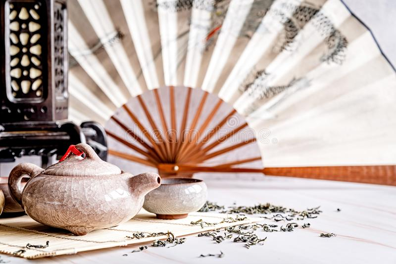 Asian teapot with teacups on bamboo tablamat decorated with chinese fan, lantern and scattered green tea on white marble royalty free stock images