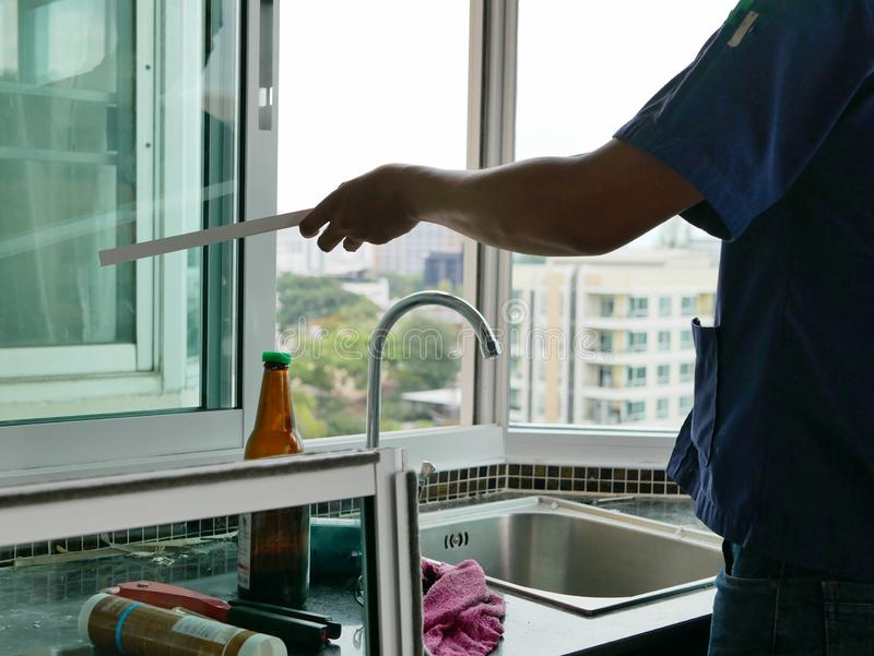 Asian technician hand manually working on an installation of a sliding window royalty free stock images