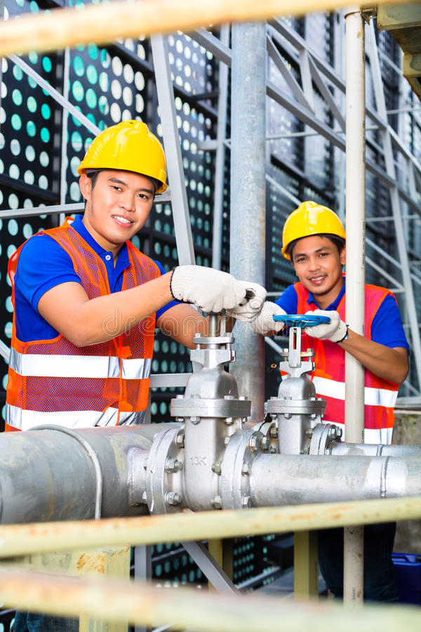 Asian Technicians or engineers working on valve royalty free stock image