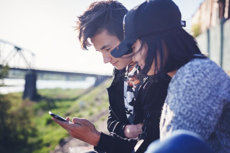 Asian teen boy and girl look in smartphone, communicate, have fun, millenial, teenagers rest together royalty free stock photo