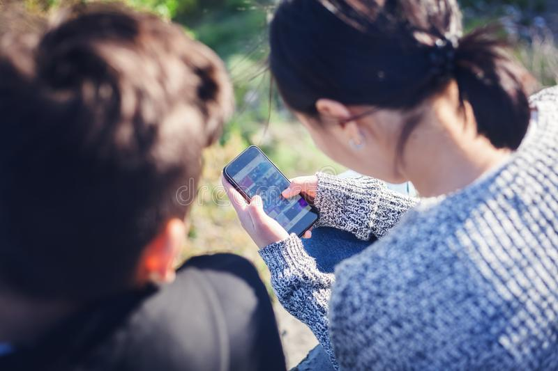 Asian teen boy and girl look in smartphone, communicate, have fun, millenial, teenagers rest together stock photography