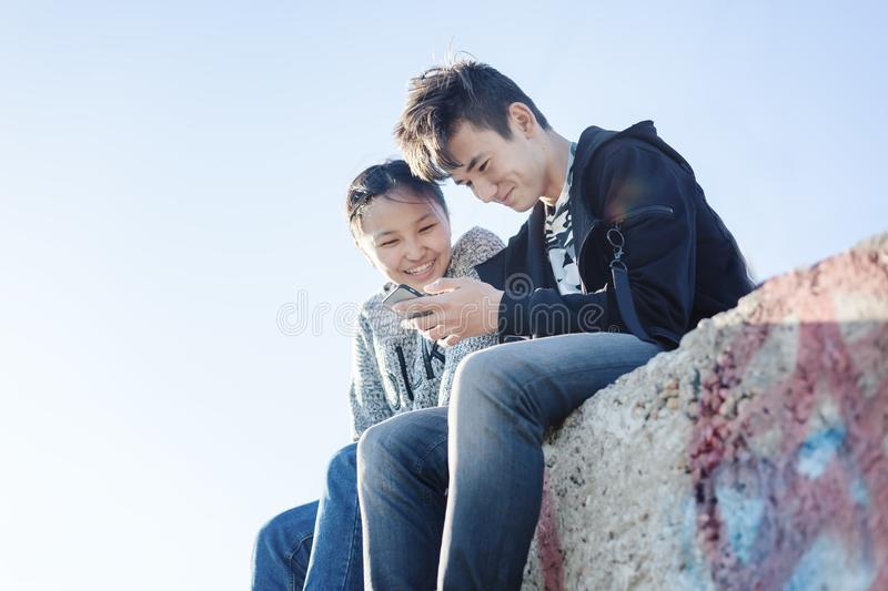 Asian teen boy and girl look in smartphone, communicate, have fun, millenial, teenagers rest together royalty free stock photography