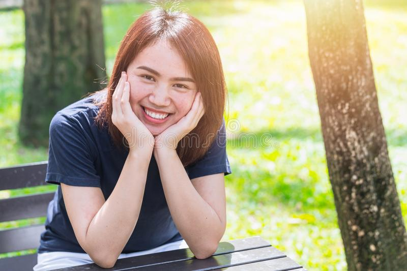 Asian teen casual cloth sitting smile with hand hold on face royalty free stock image