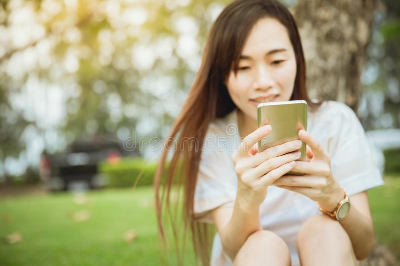 Asian teen enjoy using smartphone outdoor park relax royalty free stock photography
