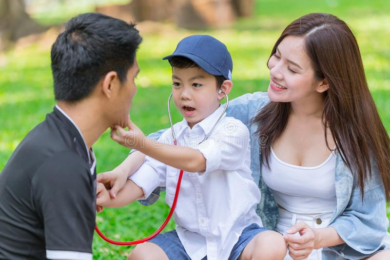 Asian teen family fun enjoy roleplay doctor in park holiday royalty free stock photos