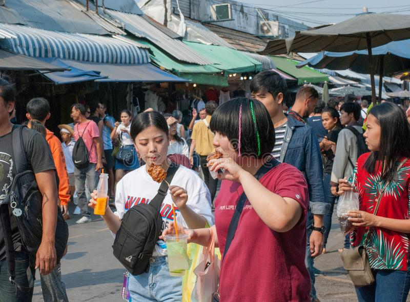 Asian teen friends walking and eating some food and drinking fruit juice royalty free stock photo