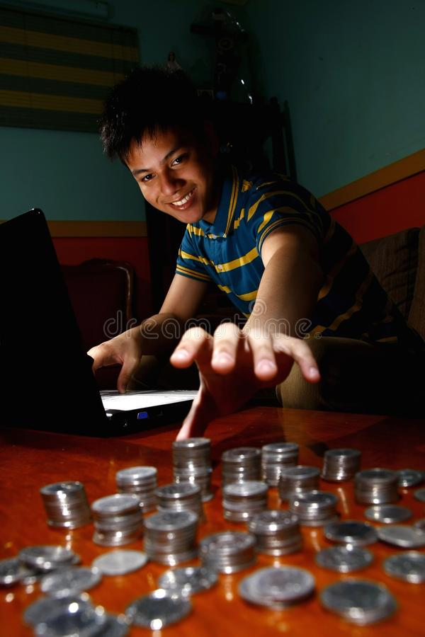 Asian Teen in front of laptop computer and reaching for a stack of coins stock images