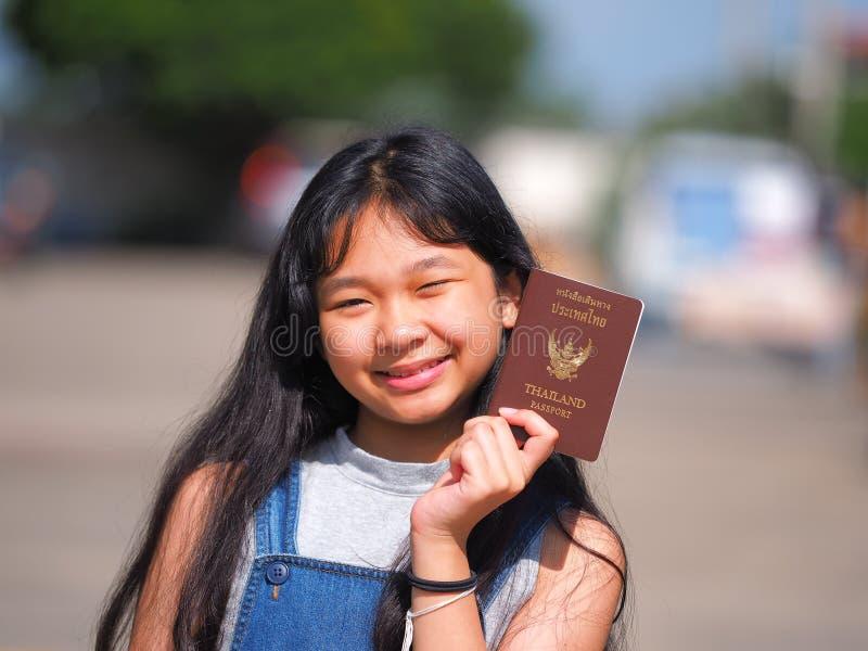 Asian teen girl with long black hair holding Thai passport stock photography