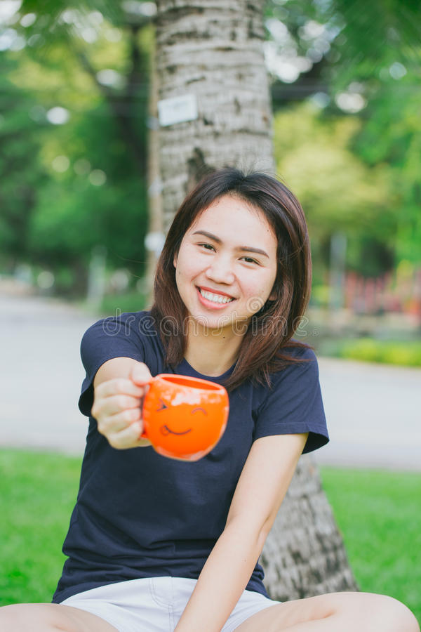 Asian teen handle smile mug in the green park stock images