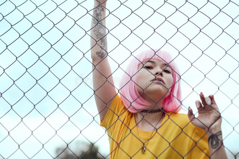 Trendy Asian teenager behind fence royalty free stock photography