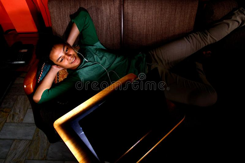 Asian teen laughing and watching video on a laptop royalty free stock photos