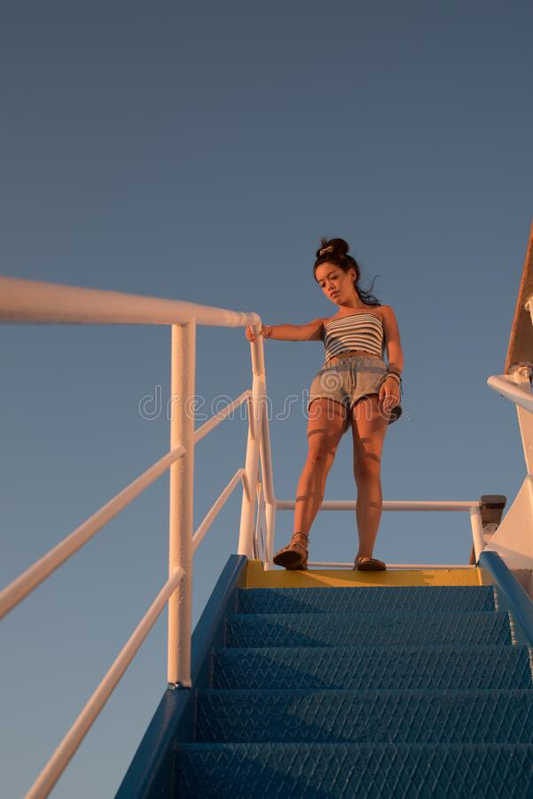 Asian teen standing on top of blue stair with yellow stripe stock photography