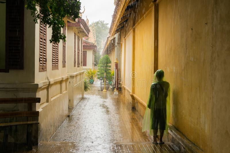 Asian teen waiting for the monsoon rain to stop stock images