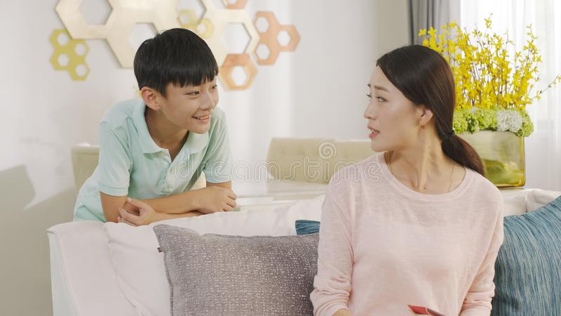 Asian teenage boy smiling & talking to his mother indoors at home stock photo
