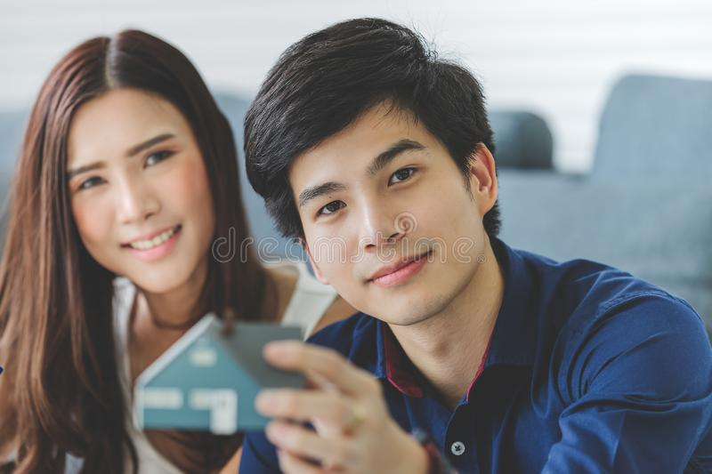 Asian teenage couple is planning to build his future house with stock photos