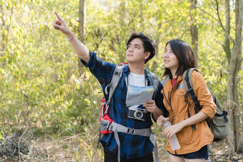 Asian teenage couples hold a map and point with hand. Couple of young tourist hiking in a forest.  stock image