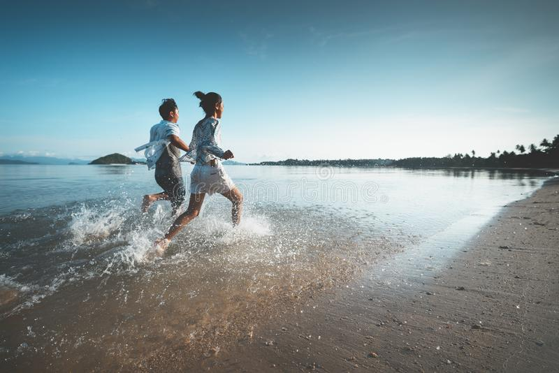 Asian teenage girl and boy running on the beach royalty free stock photos